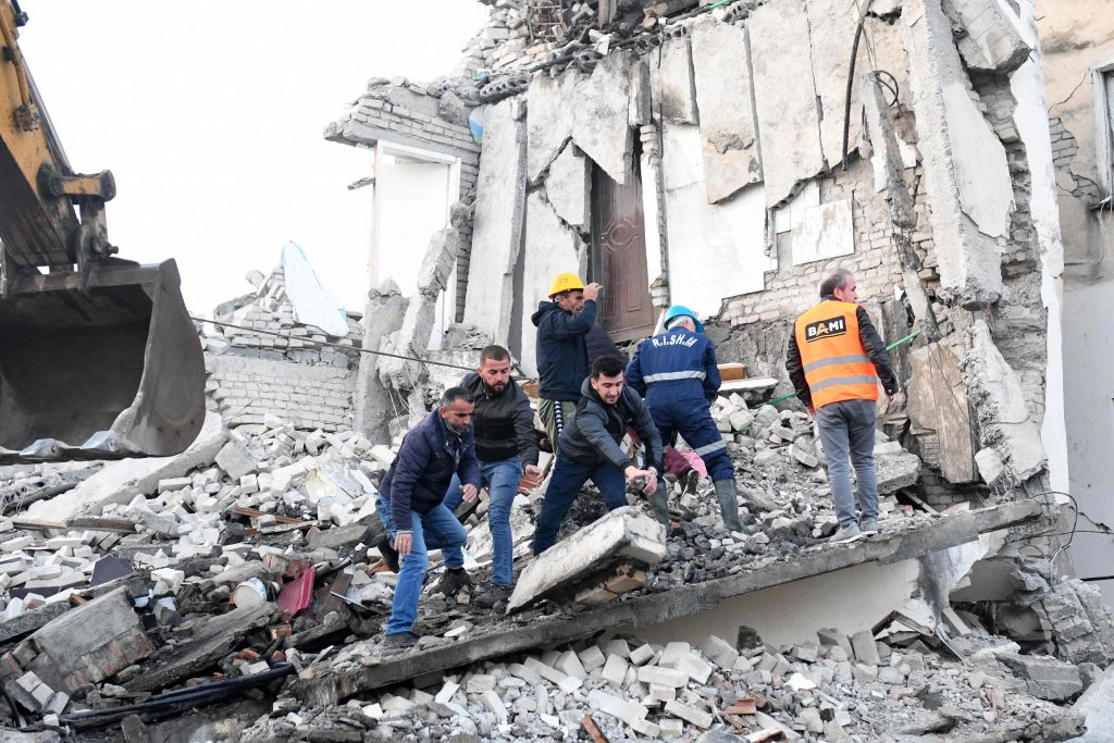 Emergency workers clear debris at a damaged building in Thumane, 34 kilometres (about 20 miles) northwest of capital Tirana, after an earthquake hit Albania, on November 26, 2019. - Four people died and some 150 were slightly injured in Albania after a 6.4 magnitude earthquake, the strongest in decades, rocked the Balkan country early Tuesday. The epicentre of the quake was about 34 kilometres (about 20 miles) northwest of Tirana, according to the European-Mediterranean Seismological Centre. (Photo by Gent SHKULLAKU / AFP)
